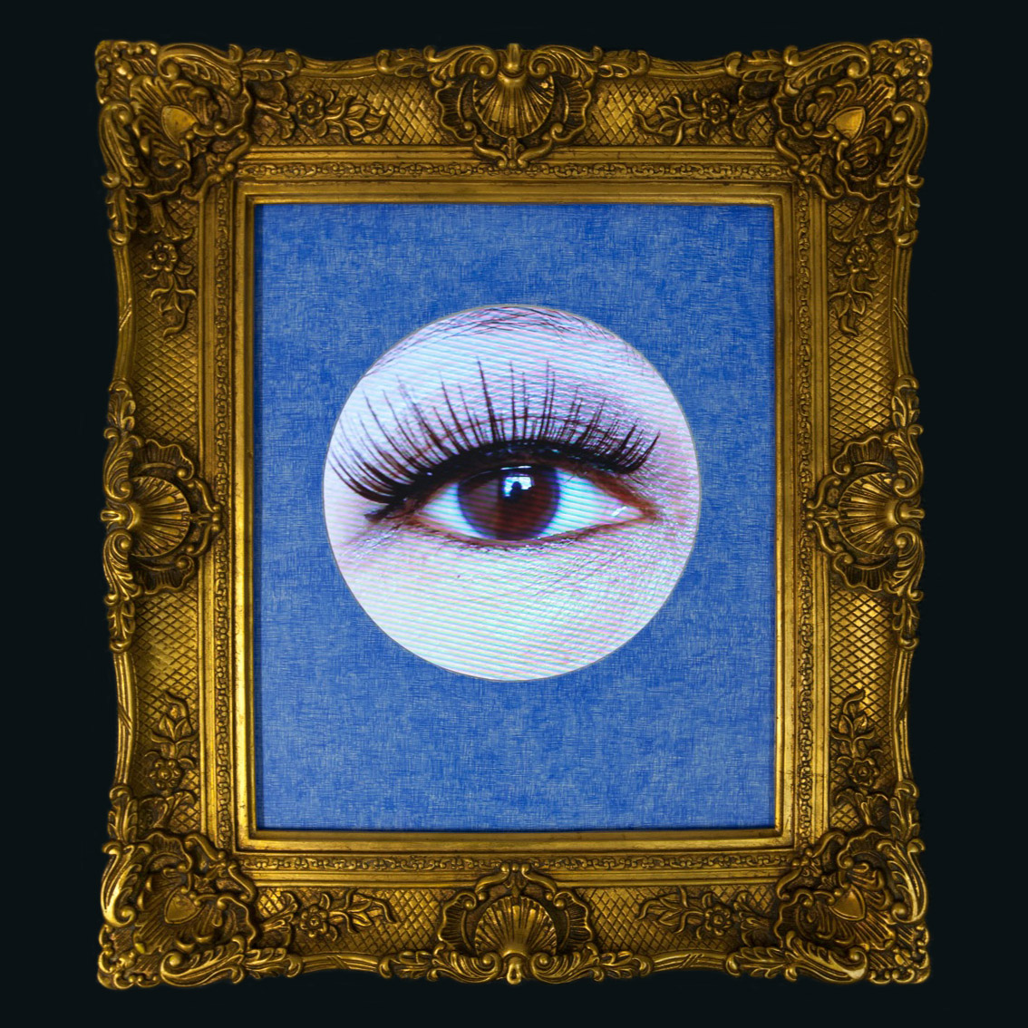A circular cut out photo of a human eye with long lashes framed in an ornate gold-coloured picture frame.